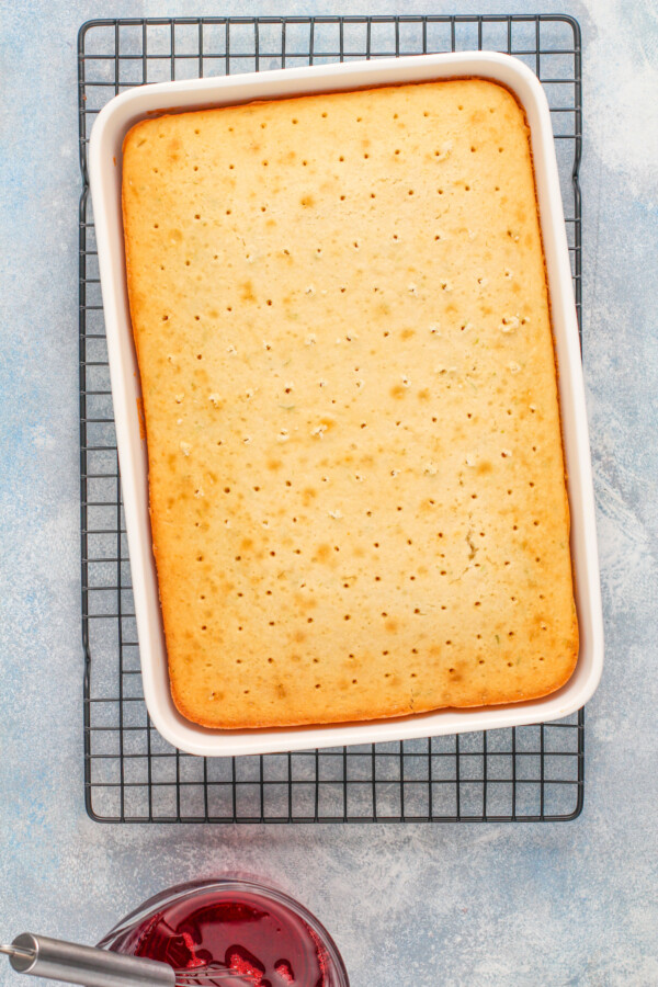 A white cake on a cooling rack with holes poked into it.