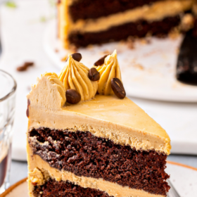A chocolate layer cake is presented on a white plate with a small cup of espresso next to it.