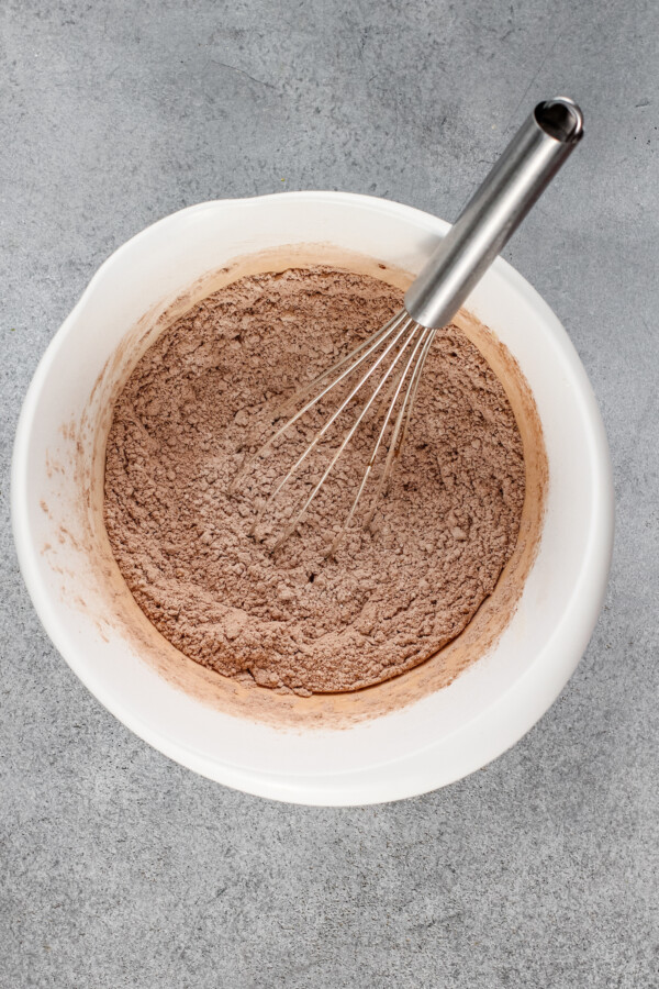 Dry ingredients are being whisked in a white mixing bowl.