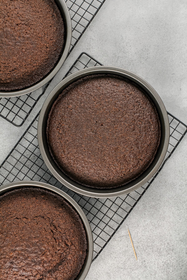Three baked cake are presented on cooling racks.