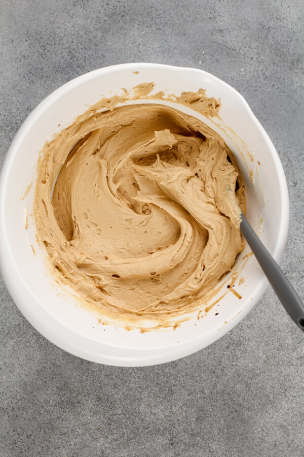 Buttercream is being mixed in a white bowl.
