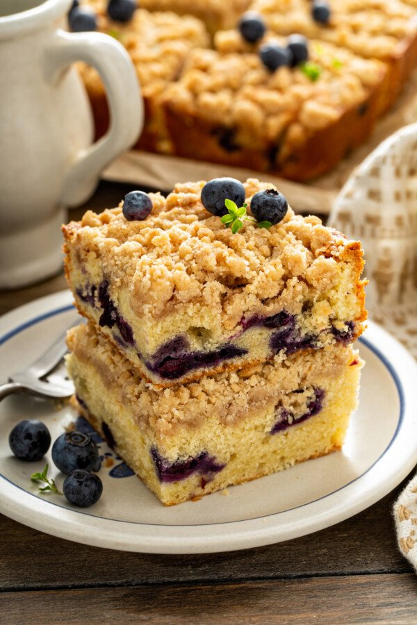 Two pieces of blueberry coffee cake stacked on top of each other on a white plate.