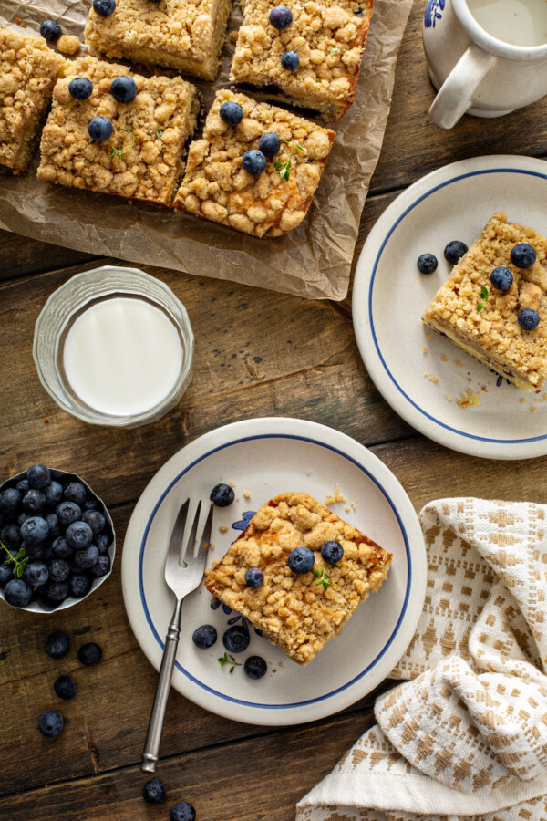 Overhead image of a glass of milk and coffee cake with a fork and coffee cake on parchment paper.