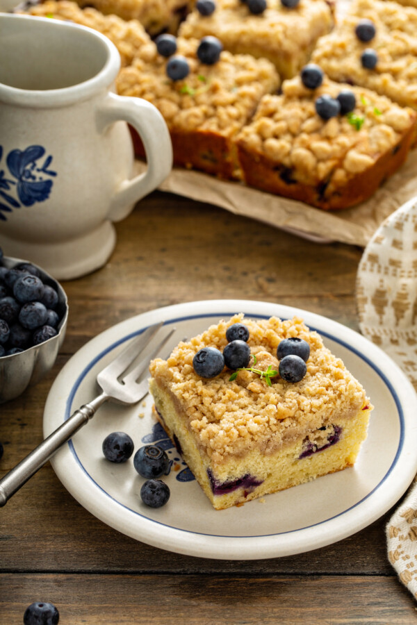 One serving of blueberry coffee cake on a white plate with a fork.