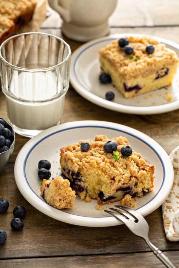 Coffee cake with blueberries on a white plate with a fork taking a bite out of it and a glass of milk.