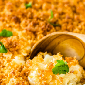 Up close image of cheesy potato casserole with parsley on top and a spoon taking a scoop.