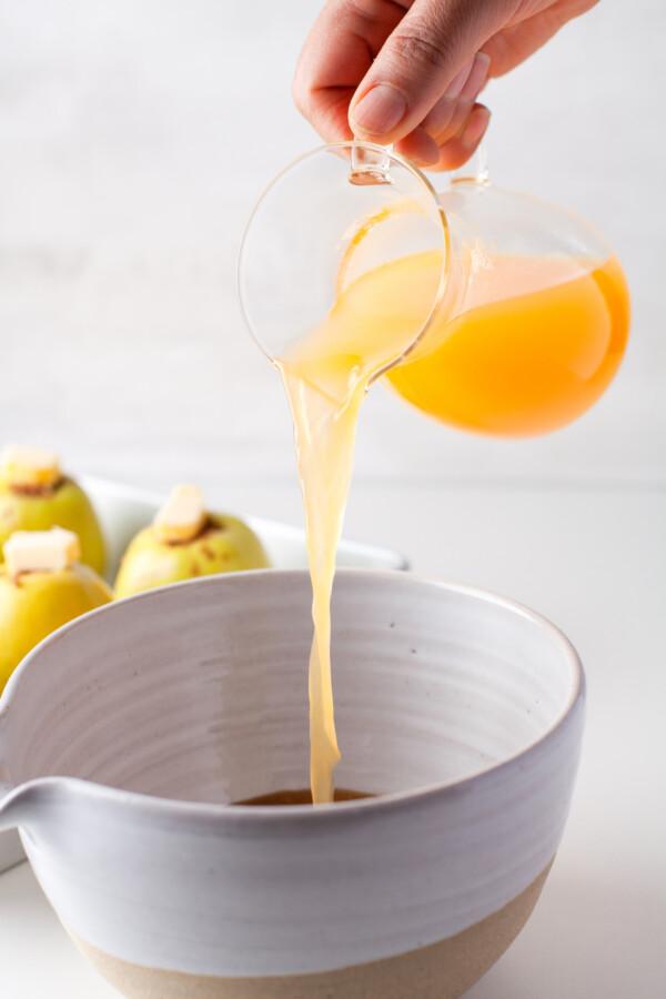 Orange juice being added to a bowl of brown sugar.