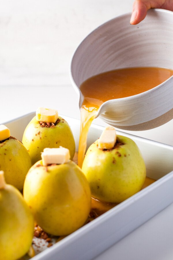 Citrus syrup being poured over stuffed apples.