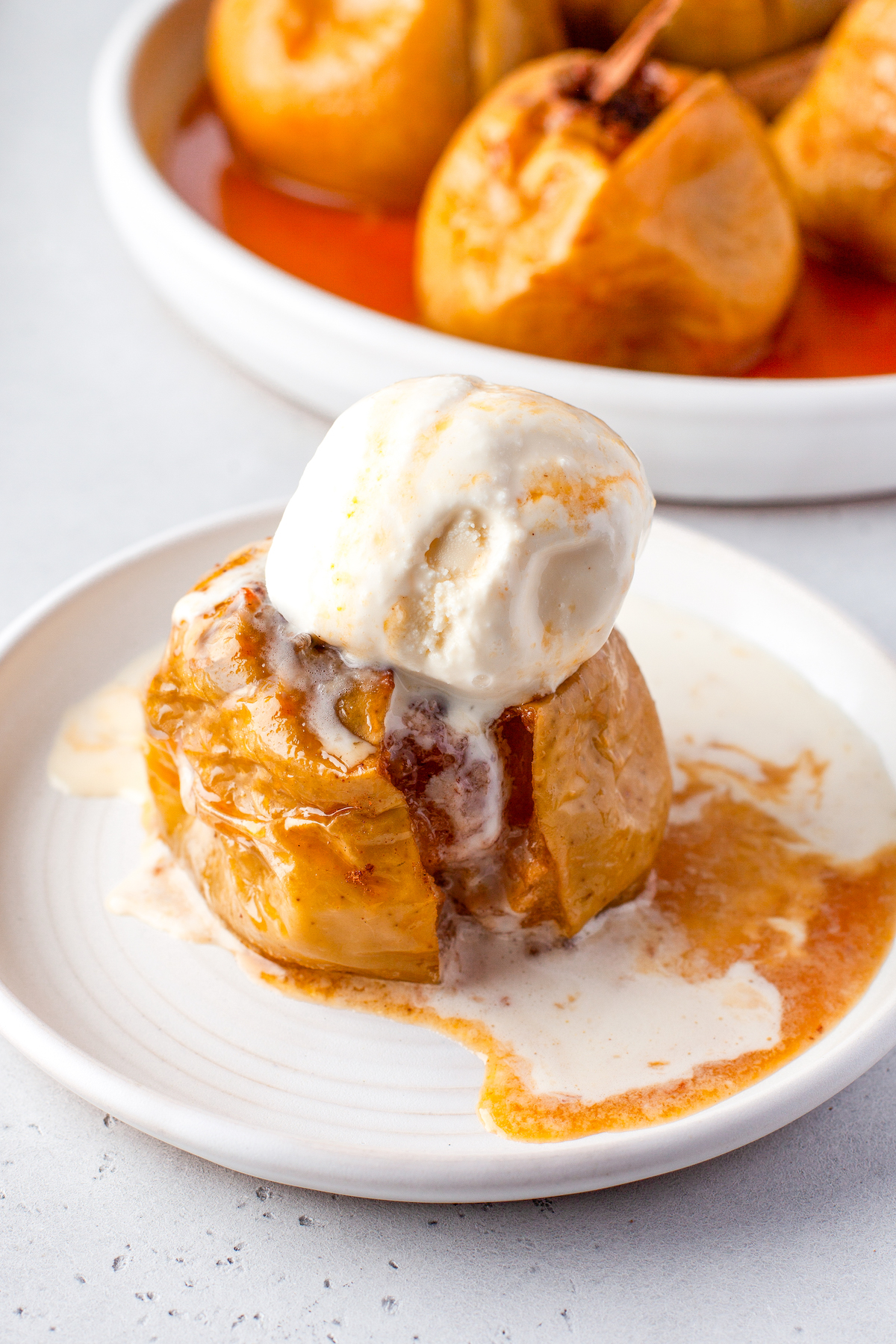 A cinnamon baked apple with a scoop of ice cream on top.