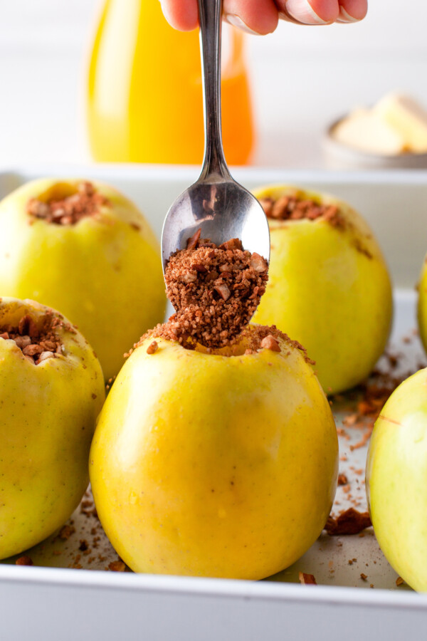 Cored apples being filled with a cinnamon mixture.