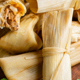 Image of tamales wrapped in corn husks on a brown cutting board.