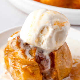 A baked apple on a white plate with sauce and vanilla ice cream on top.