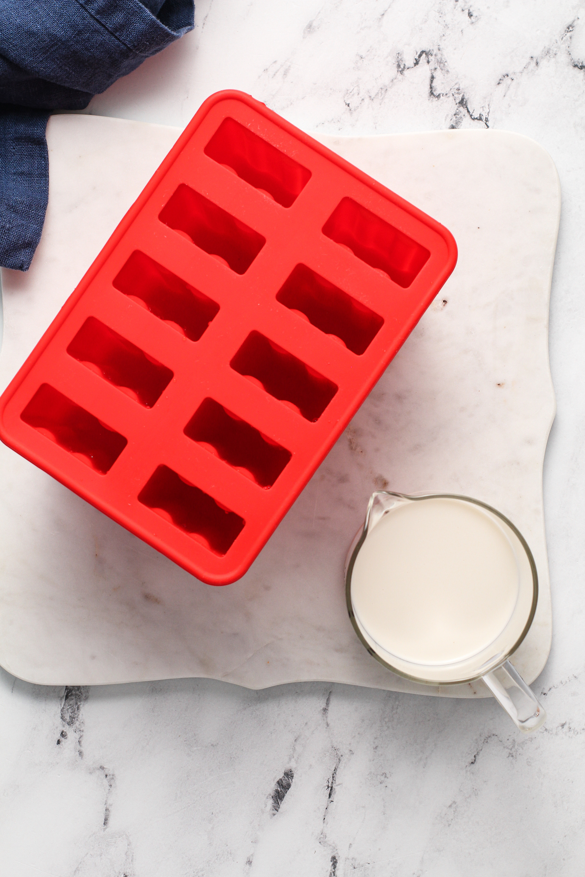 popsicle mold with oatmilk in a measuring cup