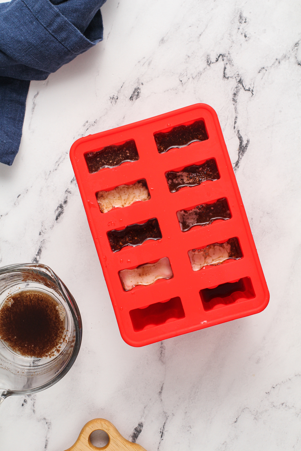 popsicle mold with espresso popsicle mixture on marble