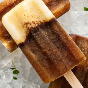 espresso popsicles over ice on a white plate.