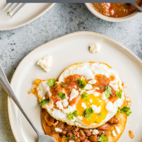 Huevos Rancheros on a white plate with a fork.