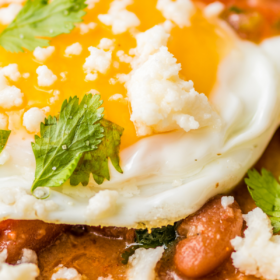 Up close image of a fried tortilla with beans on top and a fried egg.