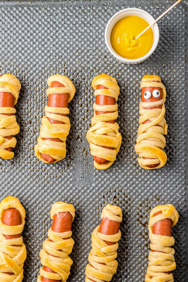 Candy eyes applied to baked hot dogs.