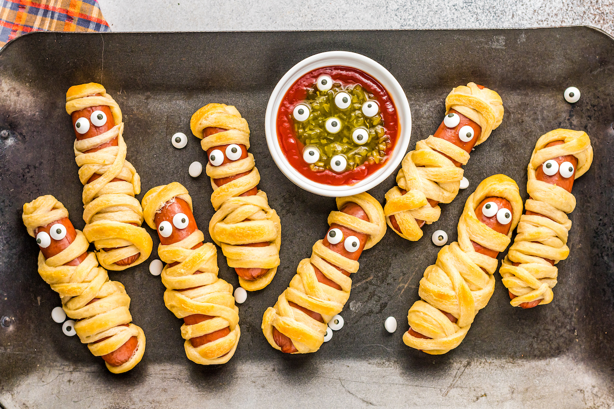 A tray of baked mummy hot dogs with monster dip.