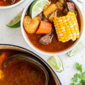 Beef Sancocho in a large pot with a ladle and in two bowls.