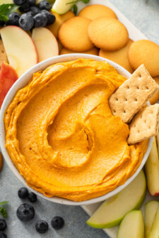 Pumpkin dip in a bowl with crackers, cookies and fruit