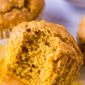 Pumpkin muffin with wrapper removed and a bite taken out of it.