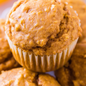 Pumpkin muffins stacked on top of each other.