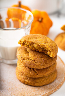 Pumpkin cookies in a stack next to a glass of milk.