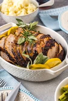 A serving dish filled with sliced turkey breast, lemon slices, and herbs.