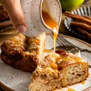 Two slices of Apple Streusel Cake on a white plate with caramel sauce being drizzled on top of one slice of cake.