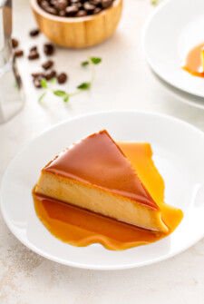 A slice of flan on a white plate.