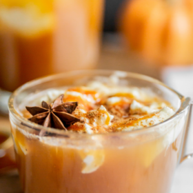 Image of pumpkin apple cider in a glass mug with whip cream.