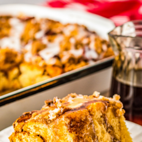 A slice of pumpkin French toast casserole on a white plate with syrup poured on top.